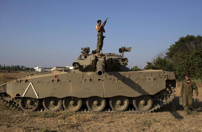 An Israeli soldier checks his weapon atop a tank near the border with Gaza July 27, 2014. REUTERS/Siegfried Modola