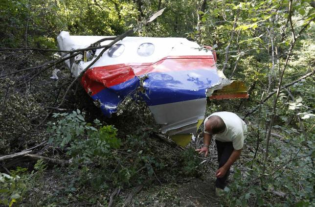 A man walks past wreckage at the crash site of Malaysia Airlines Flight MH17 near the village of Hrabove (Grabovo), Donetsk region July 26, 2014. REUTERS/Sergei Karpukhin