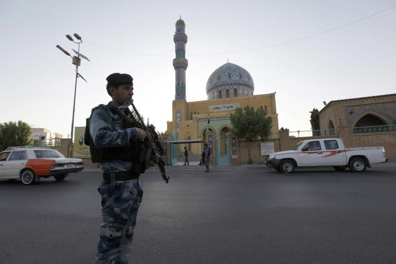 An armed Iraqi policeman stands guard outside a Sunni mosque during Eid al-Fitr prayers in Baghdad July 28, 2014.      REUTERS/Ahmed Saad