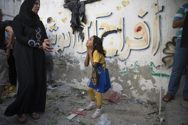 A Palestinian girl reacts at the scene of an explosion that medics said killed eight children and two adults, and wounded 40 others at a public garden in Gaza City July 28, 2014. REUTERS/Finbarr O'Reilly