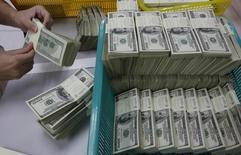 Стопки долларов США в отделении Kasikornbank в Бангкоке 21 января 2010 года. Российским властям придется изыскать до $90 миллиардов на поддержку государственных компаний и банков в случае полного отсутствия внешнего финансирования в результате очередных санкций Запада, подсчитали эксперты Высшей школы экономики. REUTERS/Sukree Sukplang