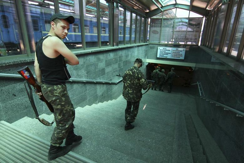 Armed pro-Russian separatists walk down a flight of stairs at a railway station in Donetsk July 21, 2014. REUTERS/Konstantin Cherginsky