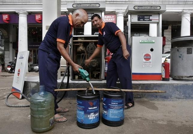 Employees manually fill containers with diesel during a power cut at a fuel station in New Delhi July 31, 2012. REUTERS/Adnan Abidi/Files