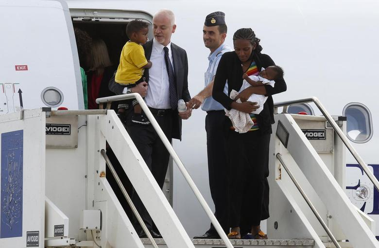 Mariam Yahya Ibrahim of Sudan (R) holds one of her children next to Lapo Pistelli (L), Italy's vice minister for foreign affairs, holding her other child, as they land at Ciampino airport in Rome July 24, 2014. REUTERS/Remo Casilli