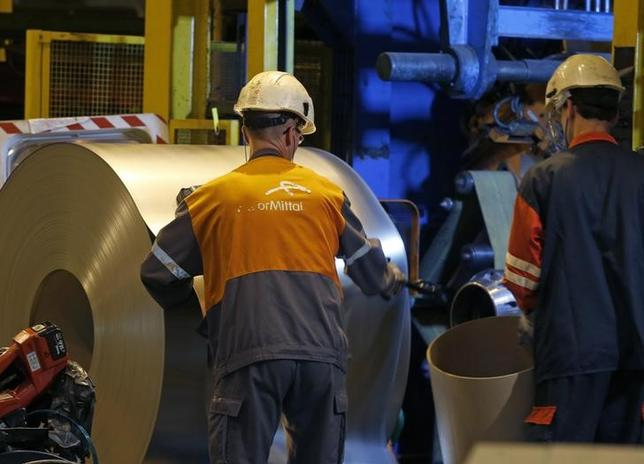 Operators work on a coil of steel at the ArcelorMittal Factory in Florange, Eastern France, October 18, 2013. REUTERS/Vincent Kessler/Files