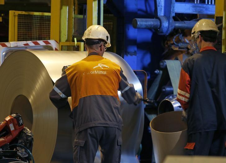 Operators work on a coil of steel at the ArcelorMittal Factory in Florange, Eastern France, October 18, 2013. REUTERS/Vincent Kessler/Files