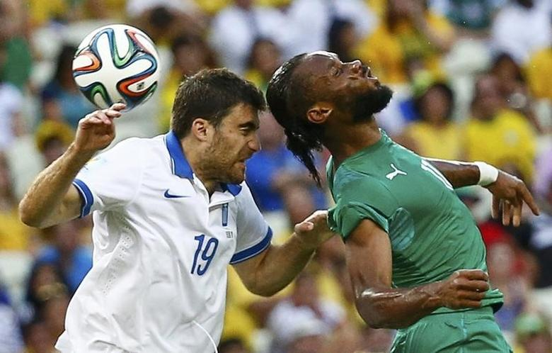 Greece's Sokratis Papastathopoulos (L) fights for the ball with Ivory Coast's Didier Drogba during their 2014 World Cup Group C soccer match at the Castelao arena in Fortaleza June 24, 2014. REUTERS/Paul Hanna