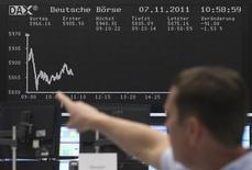 Трейдер указывает на экран с колебаниями индекса DAX на фондовой бирже во Франкфурте-на-Майне 7 ноября 2011 года. Рост немецкой экономики замедлится до нуля во втором квартале с 0,8 процента в первом из-за кризиса на Украине и жёстких новых экономических санкций, наложенных на Россию, сказал глава немецкого исследовательского института Ifo. Но официальный Берлин заявил, что санкции необходимы ради мира в Европе, невзирая на убытки. REUTERS/Alex Domanski