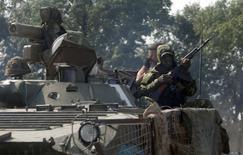 Военнослужащие украинской армии близ села Никишино в Донецкой области 4 августа 2014 года. Украинские правительственные войска отбили у пророссийских сепаратистов важный железнодорожный узел Ясиноватая на востоке страны, развивая операцию вокруг занятого боевиками Донецка, сообщил в понедельник Киев, хотя повстанцы это отрицают. REUTERS/Sergei Karpukhin