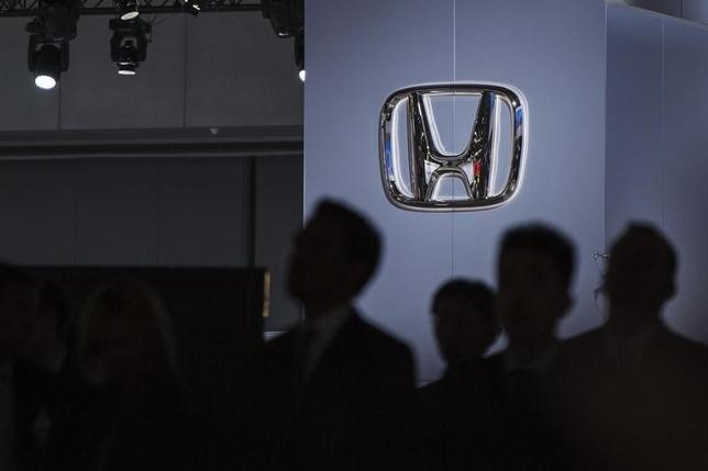 A Honda logo is pictured as car aficionados are silhouetted at the New York International Auto Show March 27, 2013. REUTERS/Lucas Jackson