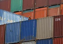 Un trabajador sobre unos contenedores almacenados en el puerto de Gujarat, India, abr 1 2014. La decisión de India de bloquear un acuerdo de la Organización Mundial de Comercio que simplificaba las normas aduaneras es un golpe potencialmente fatal para la entidad y su importancia dentro de los pactos comerciales multilaterales.    REUTERS/Amit Dave