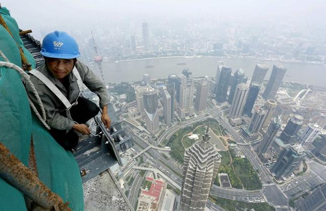 A laborer works atop the Shanghai Tower, at the financial district of Pudong, in Shanghai, August 3, 2014.REUTERS/Stringer