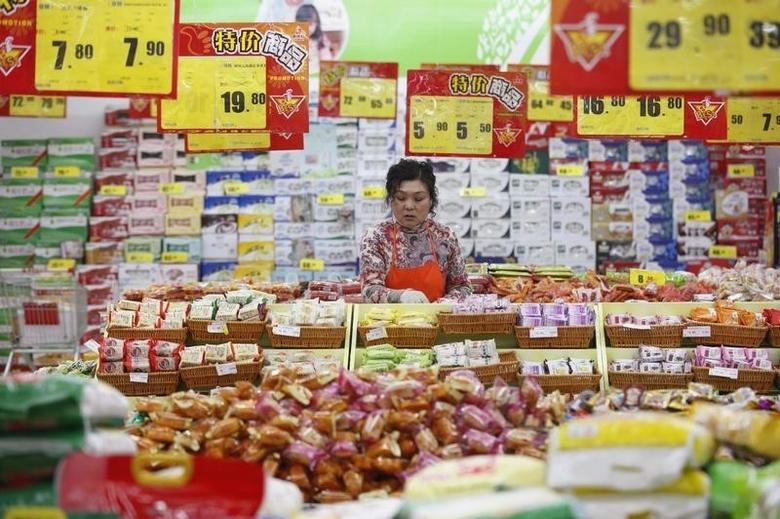 An employee arranges stock under price tags at a supermarket in Huaibei, Anhui province March 9, 2014.  REUTERS/Stringer