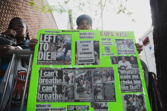 A demonstrator holds a poster critical of the New York Police Department outside the funeral of Eric Garner in New York July 23, 2014.  REUTERS/Lucas Jackson