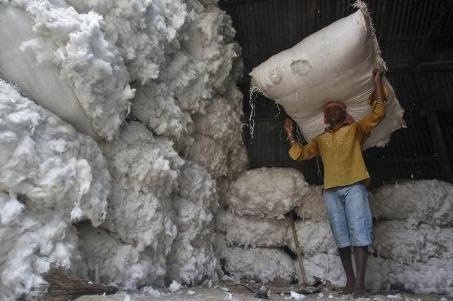 A worker carries a sack filled with cotton at a wholesale cotton market in Agartala, capital of Tripura, April 16, 2014. REUTERS/Jayanta Dey/Files
