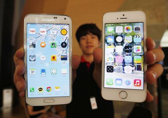 A sales assistant holding Samsung Electronics' Galaxy 5 smartphone (L) and Apple Inc's iPhone 5 smartphone (R) poses for photographs at a store in Seoul July 16, 2014. REUTERS/Kim Hong-Ji/Files