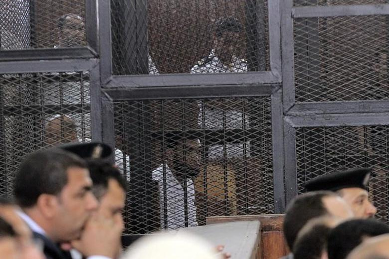 Defendants are seen behind bars during a trial of those charged with the killing of Major General Nabil Farag, at a court in Cairo June 18, 2014. REUTERS/Stringer