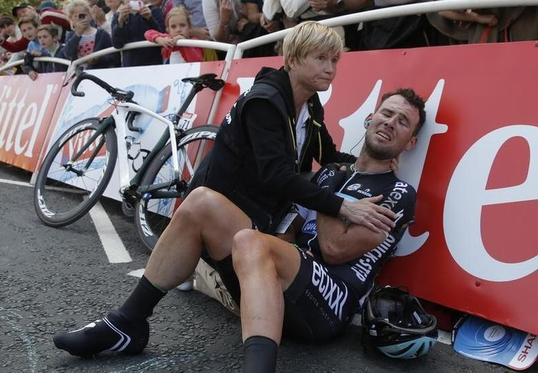 Omega Pharma-Quick Step team rider Mark Cavendish of Britain gets assistance after crashing during a mass sprint next to the finish line of the first 190.5 km stage of  the Tour de France cycling race from Leeds to Harrogate, July 5, 2014.   REUTERS/Christian Hartmann