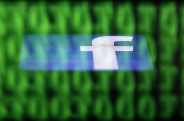 A Facebook logo on an Ipad is reflected among source code on the LCD screen of a computer, in this photo illustration taken in Sarajevo June 18, 2014. REUTERS/Dado Ruvic/Files