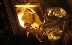 Un trabajador coloca un bloque de oro en un horno para su refinación en la mina Carlin, cerca de Elkon, EEUU, mayo 21 2014. Los precios del oro subían el jueves extendiendo el alza de la víspera, motivada por búsqueda de refugio, y según analistas podría avanzar más tras romper un nivel de resistencia técnica clave. REUTERS/Rick Wilking