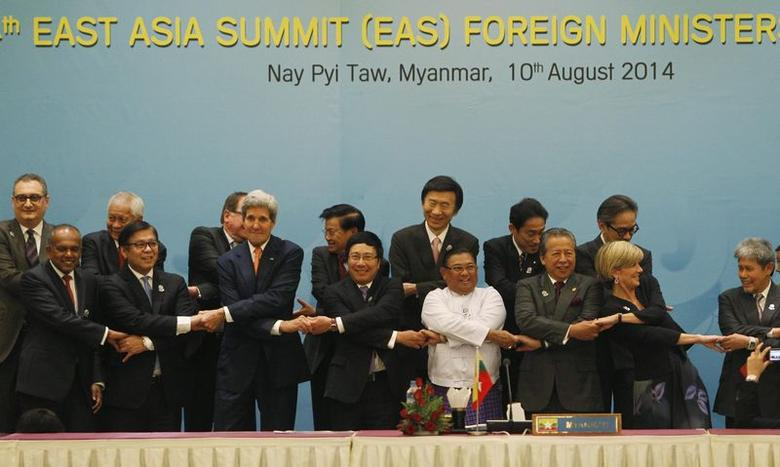 Foreign dignitaries hold hands as they pose for a photo before the 4th East Asia Summit (EAS) Foreign Ministers' meeting at the Myanmar International Convention Centre (MICC) in Naypyitaw, August 10, 2014. REUTERS/ Soe Zeya Tun
