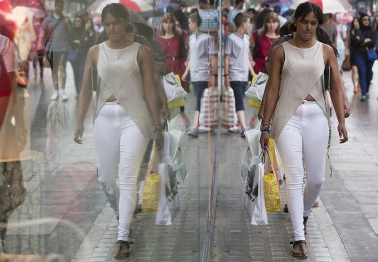 A woman carries shopping bags as she walks along Oxford Street in central London July 25, 2014. REUTERS/Neil Hall