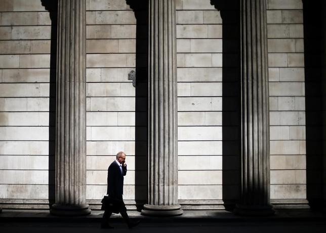 A man speaks on his phone on a sunny morning as he walks past the columns of the Bank of England in the City of London, May 19, 2014. REUTERS/Andrew Winning