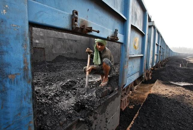 A worker unloads coal from a goods train at a railway yard in the northern Indian city of Chandigarh July 8, 2014. REUTERS/Ajay Verma