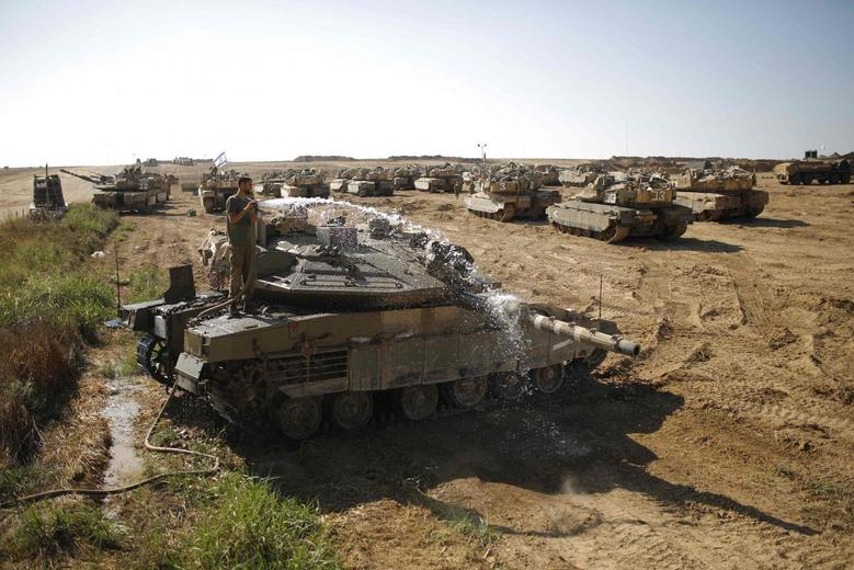 An Israeli soldier washes a tank at a staging area near the border with the Gaza Strip August 10, 2014.  REUTERS/Amir Cohen