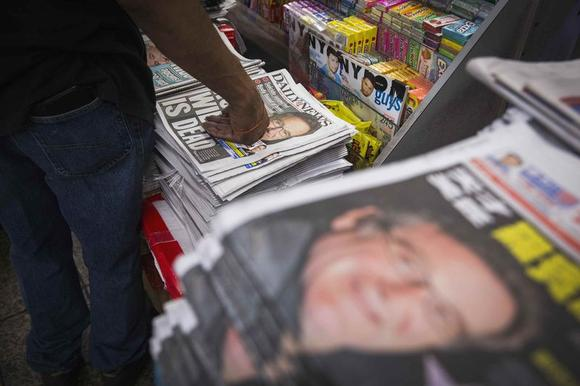 Newspapers announcing the death of comedian Robin Williams are stacked on a newsstand in New York August 12, 2014. REUTERS/Lucas Jackson