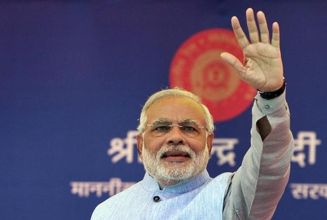 Prime Minister Narendra Modi waves to a crowd at a gathering after inaugurating a train on a new stretch of railway to the town of Katra, northwest of Jammu July 4, 2014.   REUTERS/Mukesh Gupta