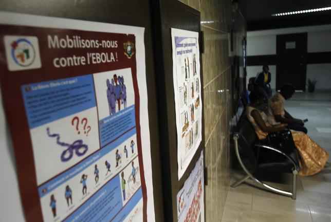People sit near a poster with a government message against Ebola, at the health minister's office in Abidjan August 11, 2014.  REUTERS/Luc Gnago