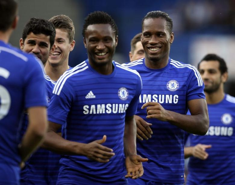 Chelsea's Didier Drogba (R) runs with his teammates as they warm up before their friendly soccer match against Real Sociedad at Stamford Bridge in London, August 12, 2014.  REUTERS/Paul Hackett