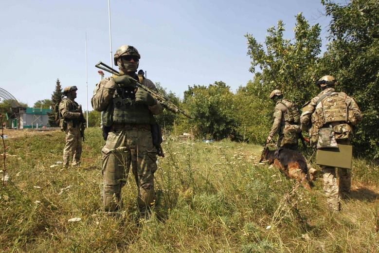 Ukrainian servicemen search for explosives with a sniffer dog around a checkpoint near the eastern Ukrainian town of Debaltseve, August 16, 2014. REUTERS/Valentyn Ogirenko