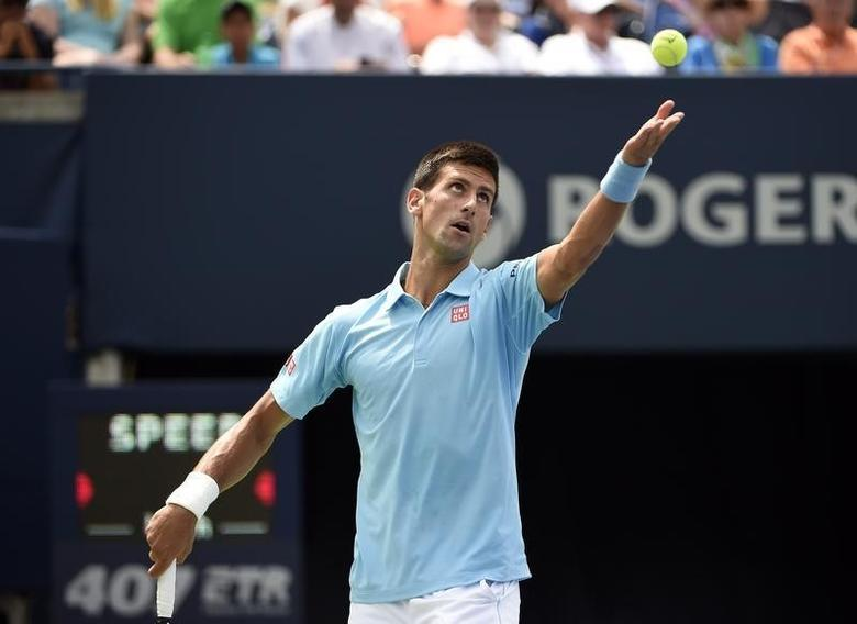 Aug 6, 2014; Toronto, Ontario, Canada; Novak Djokovic (SRB) tosses the ball to serve against Gael Monfils (FRA)  on day three of the Rogers Cup tennis tournament at Rexall Centre. Mandatory Credit: Peter Llewellyn-USA TODAY Sports