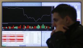 """Мужчина у экрана с котировками на Московской бирже 14 марта 2014 года. Акции ВТБ прибавили в четверг чуть больше остальных """"голубых фишек"""", несмотря на очередные слабые квартальные результаты, и рынок в целом удерживается от коррекции, ожидая новых сигналов разрядки геополитической напряженности. REUTERS/Maxim Shemetov"""