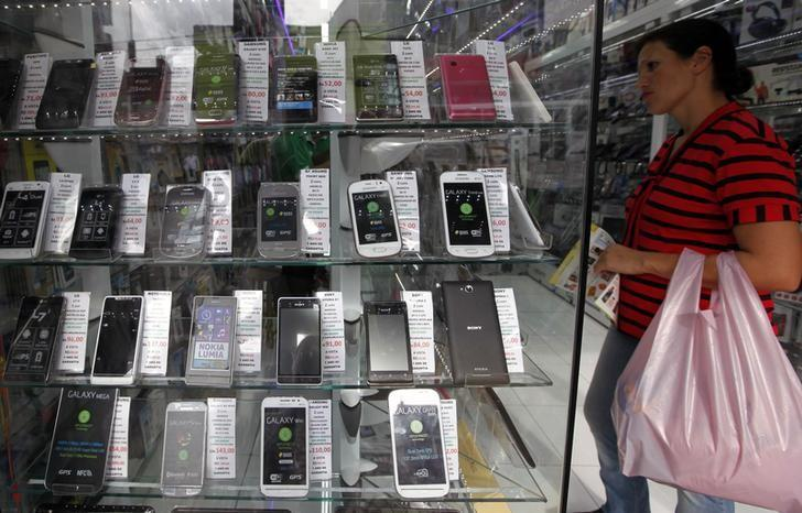A woman looks at merchandise in a mobile phone store in Sao Paulo April 23, 2014.  REUTERS/Paulo Whitaker