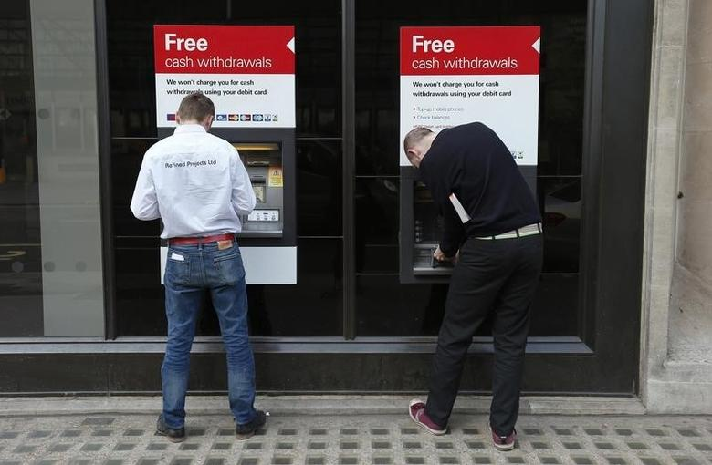 Two men use automated teller machines (ATMs) outside a HSBC bank in London March 13, 2014.    REUTERS/Suzanne Plunkett