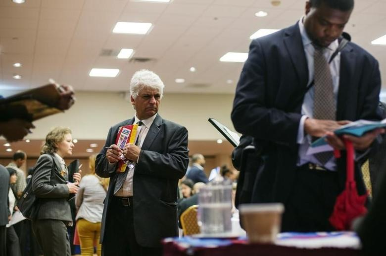 A man walks past job seekers as they fill out job applications for recruiters during a job fair in New York, June 11, 2013. REUTERS/Lucas Jackson