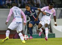 Lucas, do PSG, disputa lance com jogadores do Evian nesta sexta-feira.   REUTERS/Robert Pratta