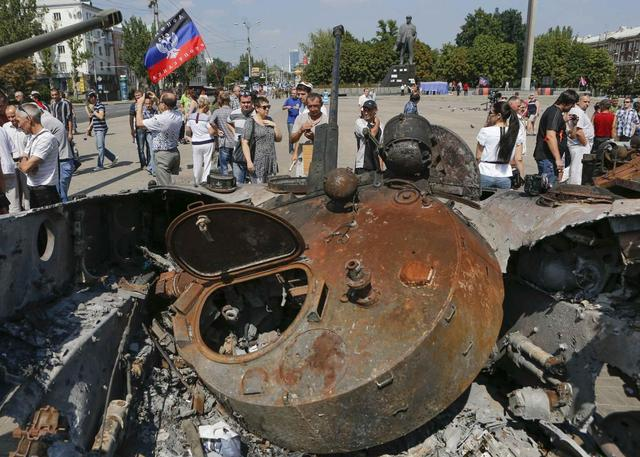 People look at destroyed Ukrainian army vehicles that were seized, after they were placed on public display at the central square in Donetsk August 24, 2014. REUTERS/Maxim Shemetov