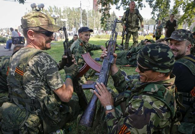 Pro-Russian separatists hold their weapons as they rest after a rally in Donetsk August 24, 2014.  REUTERS/Maxim Shemetov