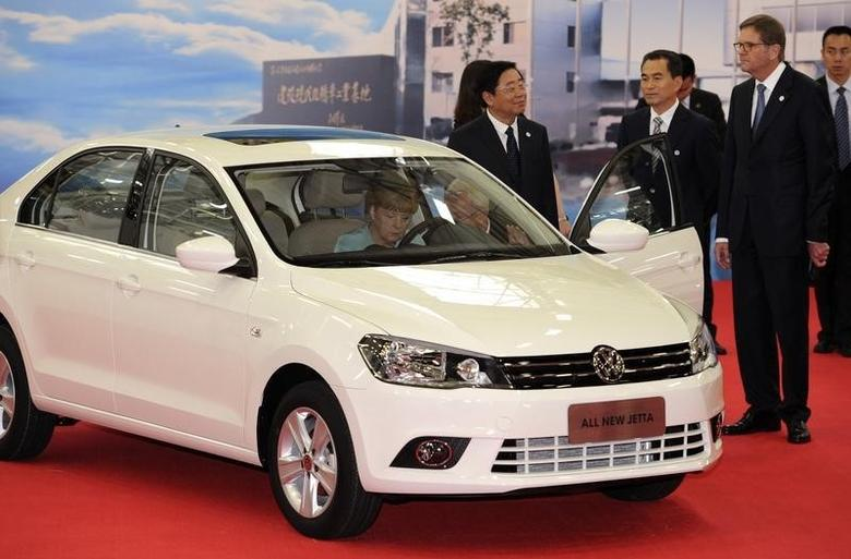 German Chancellor Angela Merkel (L) sits in an All New Jetta as she visits the FAW-Volkswagen production plant with FAW Group President Xu Jianyi (C) and Volkswagen CEO Martin Winterkorn, in Chengdu, Sichuan province July 6, 2014. REUTERS/China Daily