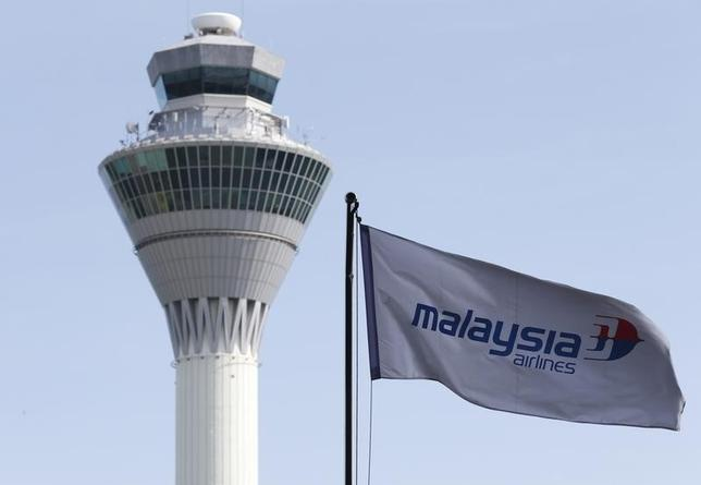 A Malaysian Airlines flag flies in front of the traffic control tower at Kuala Lumpur International Airport in Sepang July 18, 2014.  REUTERS/Olivia Harris