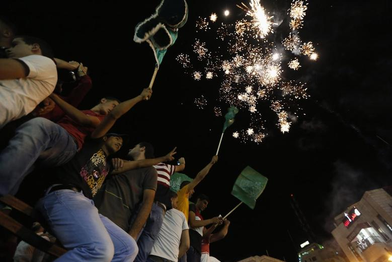 Palestinians release fireworks as they celebrate what they said was a victory by Palestinians in Gaza over Israel following a ceasefire, in the West Bank city of Ramallah August 26, 2014.  REUTERS/Mohamad Torokman