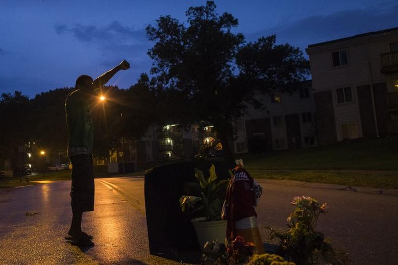 A local resident stands with his arm up over a makeshift memorial at the site where unarmed teen Michael Brown was shot dead in Ferguson, Missouri August 27, 2014.   REUTERS/Adrees Latif