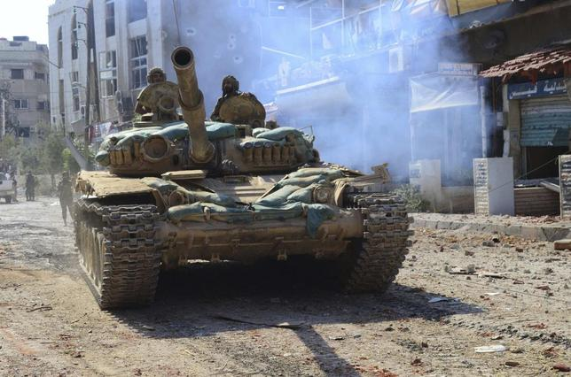 Syrian government forces stand in a tank at the town of Mleiha near Damascus August 14, 2014 in this picture released by Syria's national news agency SANA. REUTERS/SANA/Handout via Reuters