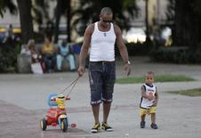 A man walks with his son in Havana September 1, 2014. Picture taken September 1, 2014.   REUTERS/Enrique De La Osa