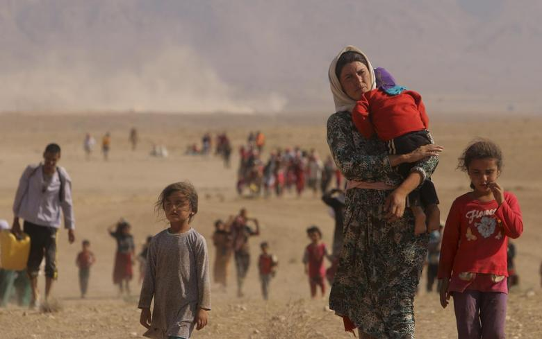 Displaced people from the minority Yazidi sect, fleeing violence from forces loyal to the Islamic State in Iraq, walk towards the Syrian border, on the outskirts of Sinjar mountain, near the Syrian border town of Elierbeh of Al-Hasakah Governorate August 11, 2014. REUTERS/Rodi Said