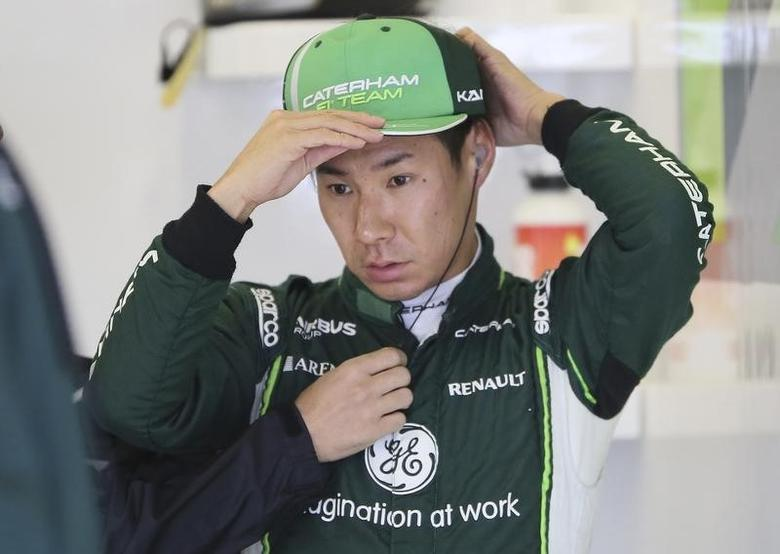 Caterham Formula One driver Kamui Kobayashi of Japan adjusts his cap during final practice ahead of the British Grand Prix at the Silverstone Race Circuit, central England, July 5, 2014. REUTERS/Paul Hackett